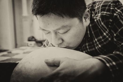 準父親親吻母親的肚子畫面
