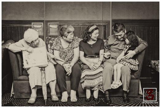小朋友坐爺爺的大腿上,爺爺在問小妹妹這是誰,看的出來妹妹有點靦腆害羞