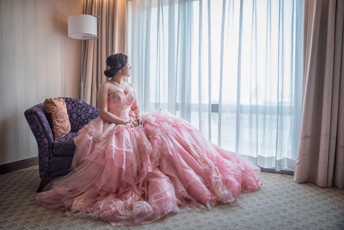 坐在窗戶旁的新娘晚禮服